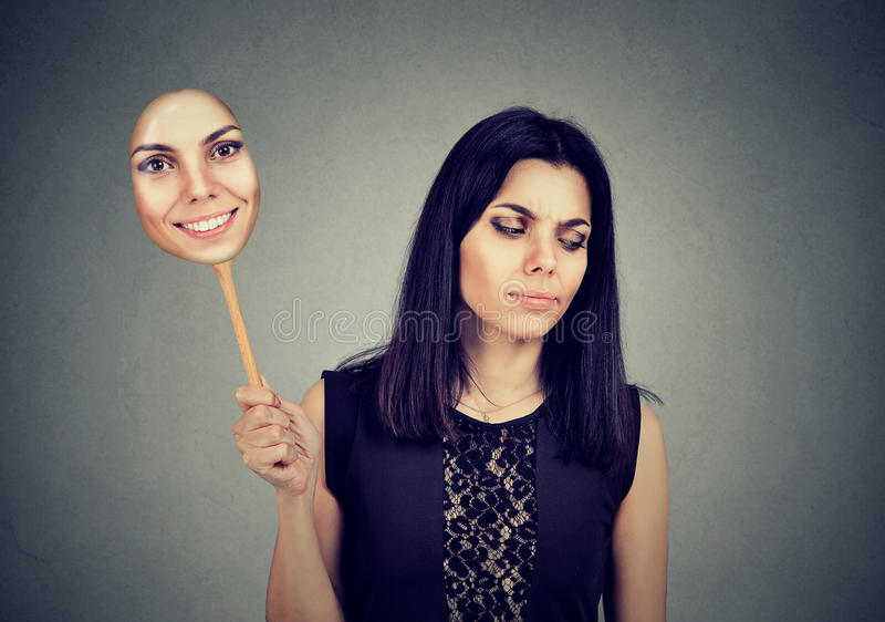 Frau mit dem traurigen Ausdrucknehmen einer Maske, die Fröhlichkeit ausdrückt stockbild