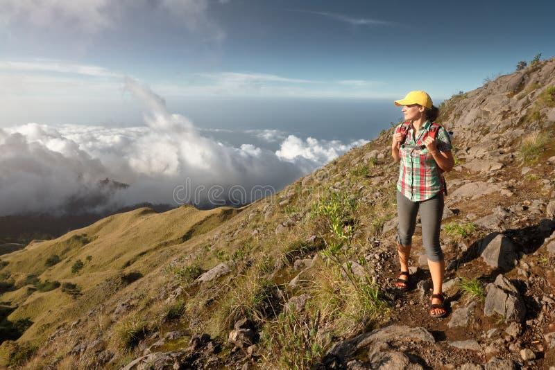 Frau mit dem Wanderer, der Ansichtsonnenuntergang in den Bergen genießt lizenzfreies stockfoto