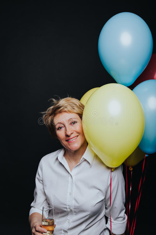 Frau mit dem Weinglas- und Ballonlächeln stockbild