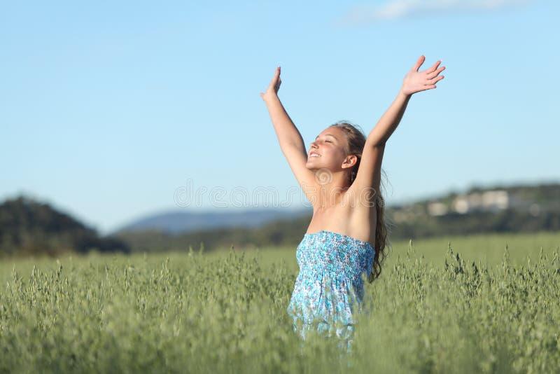 Frau mit den angehobenen Armen in einer grünen Wiese den Wind genießend stockfotografie