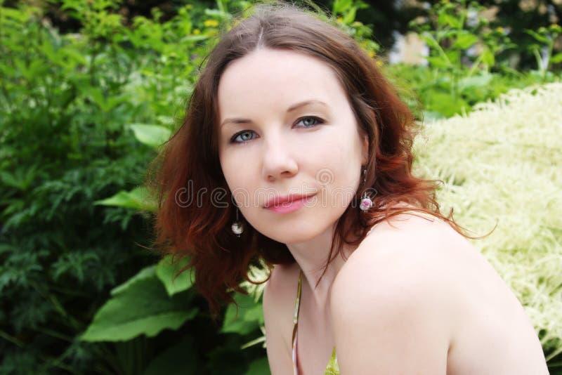 Frau mit den Blumen, die im Sommerpark aufwerfen lizenzfreies stockbild