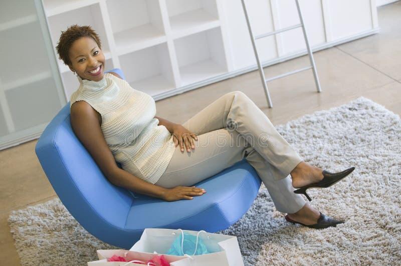 Frau mit den Einkaufen-Beuteln, die auf Stuhl sich entspannen lizenzfreies stockbild