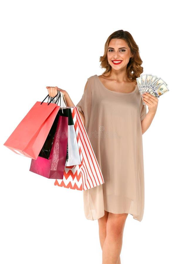 Frau mit den Einkaufstaschen, die Gelddollar auf Weiß halten, lokalisierte Hintergrund lizenzfreie stockfotografie