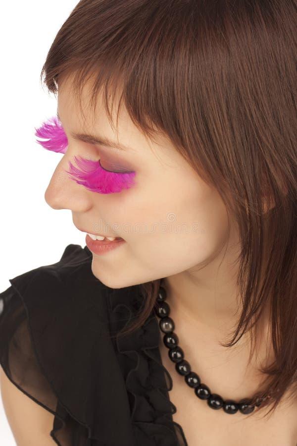 Frau mit den falschen Wimpern der rosafarbenen langen Feder stockfotografie