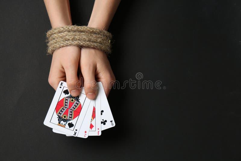 Frau mit den gebundenen Händen und den Spielkarten auf dunklem Hintergrund Konzept der Suchts stockfotos