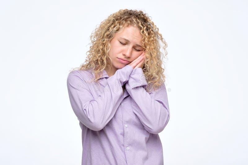 Frau mit den gefalteten Händen nahe der Backe und geschlossenen Augen, die, Rest habend schläfrig sich fühlen lizenzfreie stockbilder