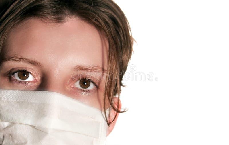 Frau mit den großen grünen Augen, die medizinische Maske tragen lizenzfreies stockbild