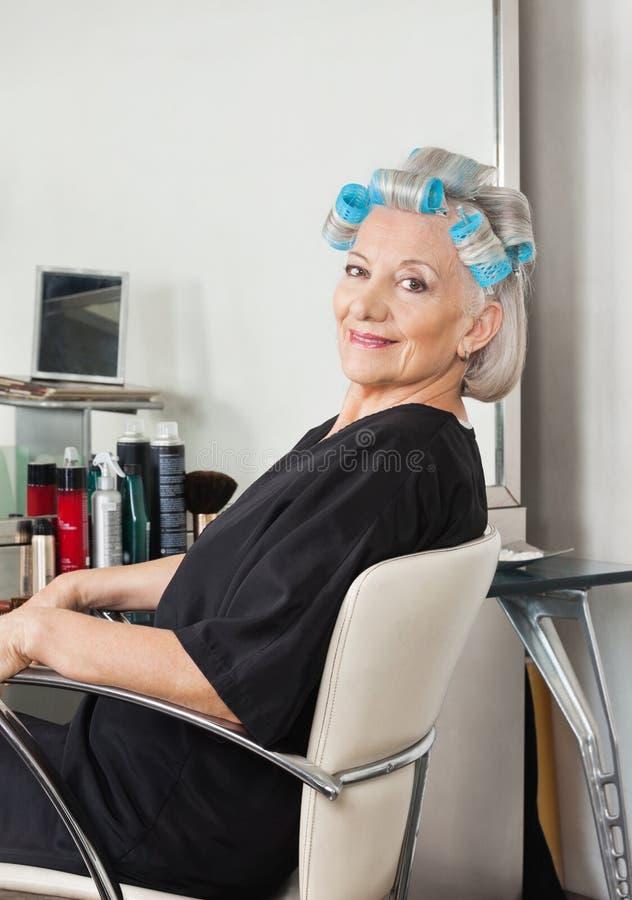 Frau mit den Haar-Lockenwicklern, die auf Stuhl am Salon sitzen lizenzfreie stockfotos