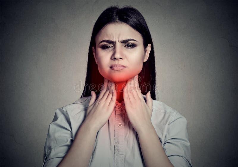 Frau mit den Halsschmerzen, die ihren Hals gefärbt im Rot berühren stockfotografie