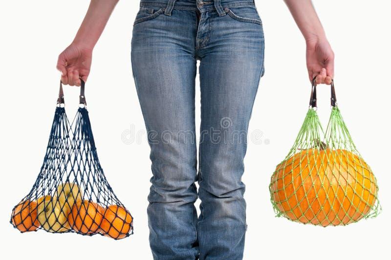 Frau mit den Jeans, die gelbe Früchte tragen lizenzfreie stockfotos