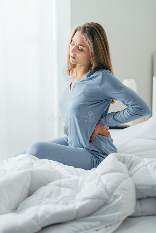 Frau mit den rückseitigen Schmerz stockbild