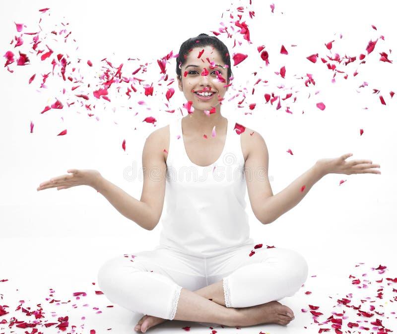 Frau mit den rosafarbenen Blumenblättern des Flugwesens lizenzfreie stockbilder