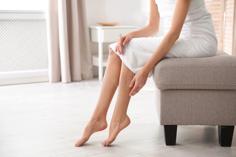 Frau mit den schönen Beinen und den Füßen, die zuhause auf Osmanen, Nahaufnahme mit Raum für Text sitzen stockfoto