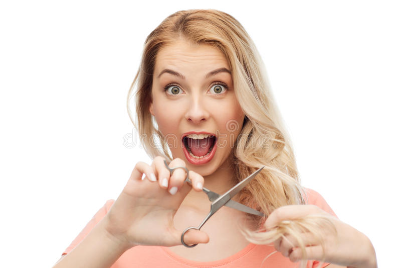 Frau mit den Scheren, die Enden ihres Haares schneiden lizenzfreie stockfotografie