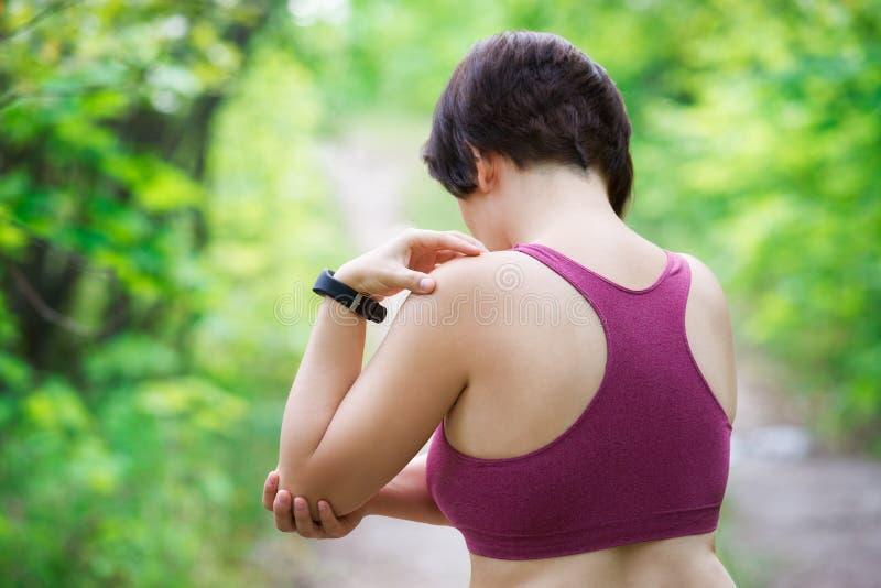 Frau mit den Schmerz in der Hand, Schulterverletzung, Trauma während des Trainings stockfoto