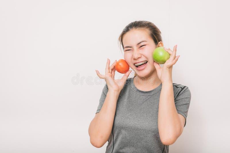 Frau mit den zahnmedizinischen Klammern, die Spaß mit grünem Apfel und Tomate haben stockfotos