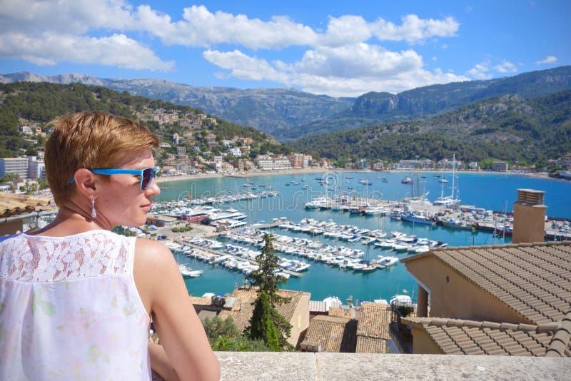 Frau mit der blauen Sonnenbrille, die Dachspitzen Port de Soller, Mallorca, Spanien betrachtet stockfotografie