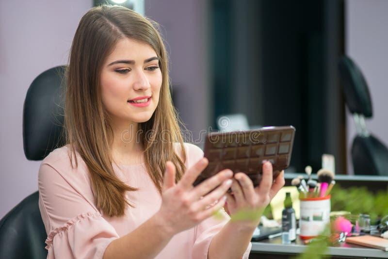 Frau mit der Frisur und Make-up, die den Spiegel im Schönheitssalon betrachten stockbilder