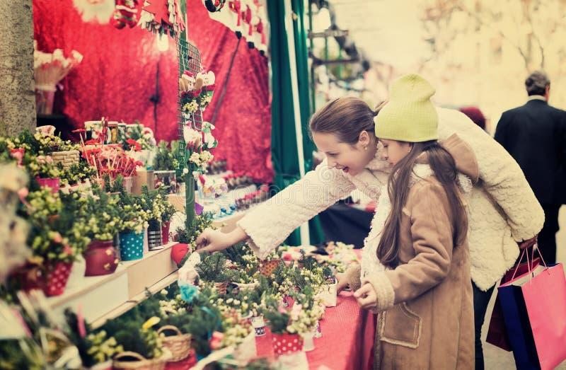 Frau mit der kleinen Tochter, die Blumenzusammensetzung kauft lizenzfreie stockfotos