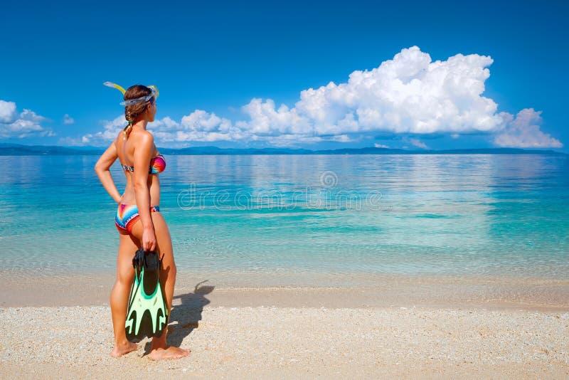 Frau mit der Maske, die geht, im tropischen Meer zu schnorcheln stockfotos