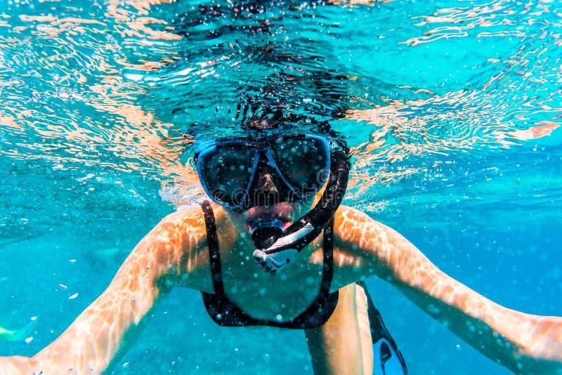 Frau mit der Maske, die im klaren Meerwasser schnorchelt lizenzfreie stockbilder