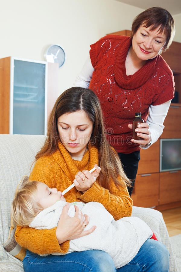 Frau mit der reifen Mutter, die für krankes Baby sich interessiert lizenzfreies stockbild