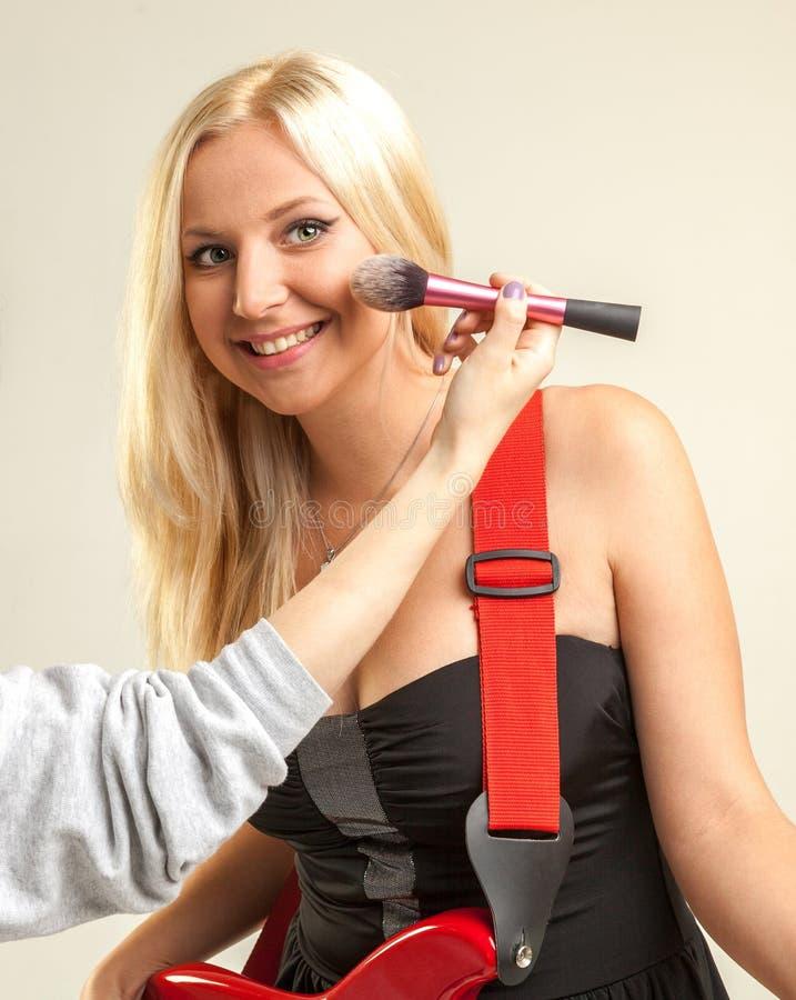 Frau mit der roten E-Gitarre, die Rouge anwendet lizenzfreies stockfoto