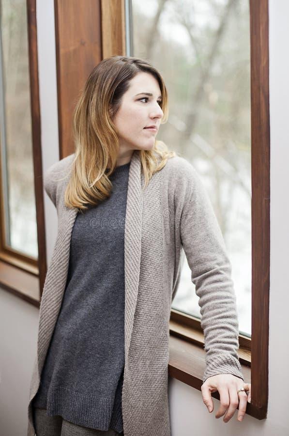 Frau mit der Winterkrise, die heraus Fenster schaut stockfotografie