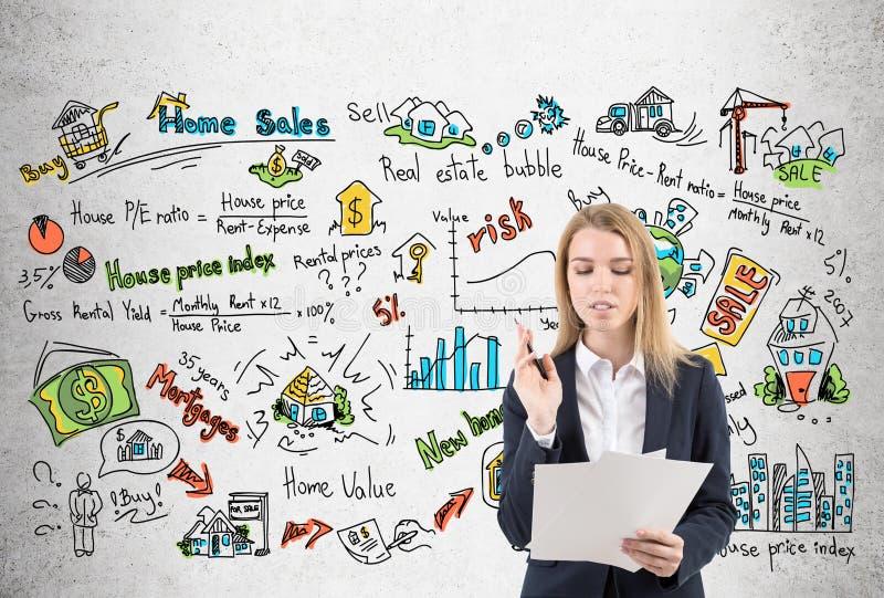 Frau mit Dokumenten und Immobilienikonen stockfoto