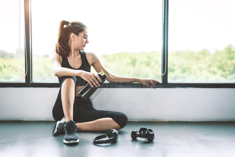 Frau mit Dummkopf- und Gerätübungslebensstiltraining, beim Turnhalleneignungsbrechen entspannen sich nach Sporttraining mit Prote stockbild