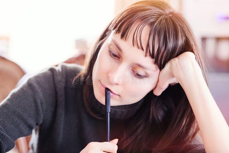 Frau mit einem Bleistiftdenken lizenzfreie stockbilder