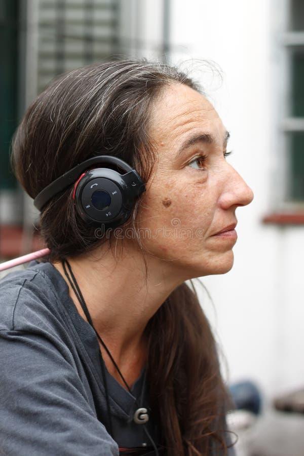 Frau mit einem Bluetooth-Kopfhörer lizenzfreie stockfotos