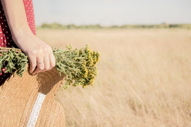 Frau mit einem Blumenstrauß und einen Hut auf dem Gebiet lizenzfreies stockbild