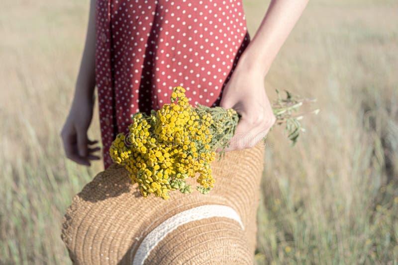 Frau mit einem Blumenstrauß und einen Hut auf dem Gebiet stockfotos