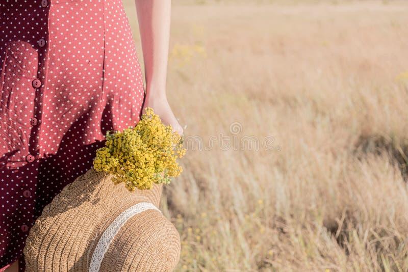 Frau mit einem Blumenstrauß und einen Hut auf dem Gebiet lizenzfreie stockbilder