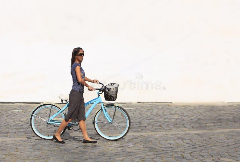 Frau mit einem Fahrrad in einer Stadt lizenzfreie stockbilder