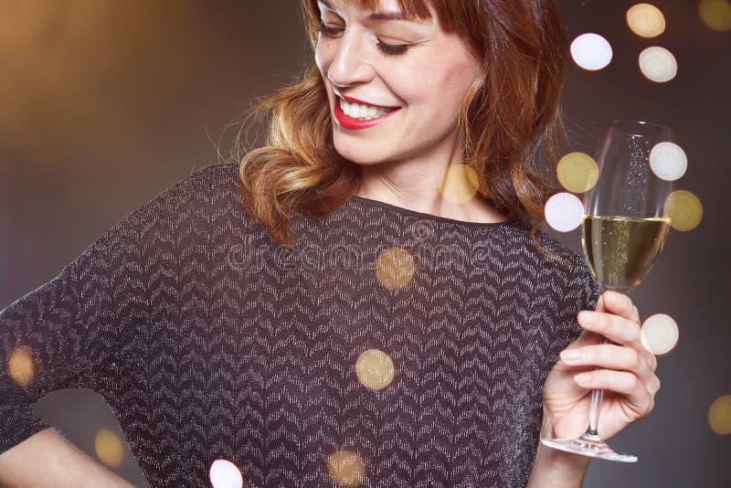Frau mit einem Glas Champagner auf dunklem Hintergrund mit Aufflackern und bokeh Dame mit dem langen gelockten Haar und den perfe stockfotografie