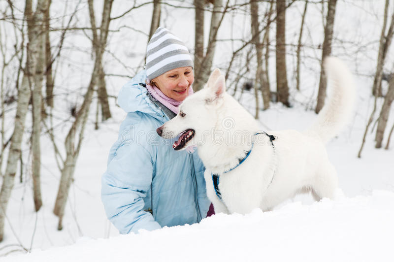 Frau mit einem Hund im Winter auf Weg stockfoto