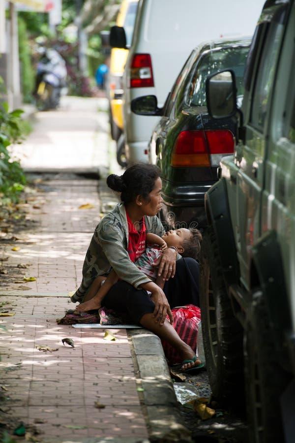 Frau mit einem Kind auf einer Beschränkung in Bali, Indonesien stockfotos