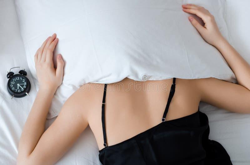 Frau mit einem Kissen über ihrem Kopf lizenzfreie stockfotografie