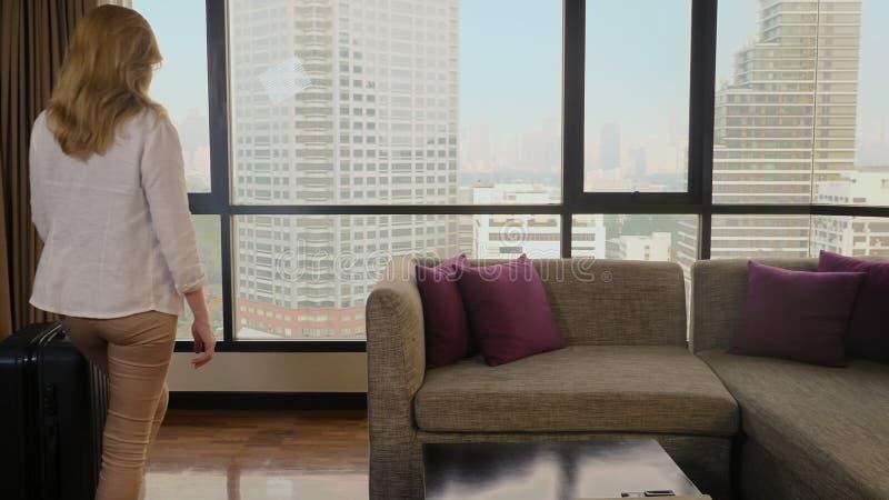 Frau mit einem Koffer auf dem Hintergrund von Wolkenkratzern in einem panoramischen Fenster lizenzfreie stockfotos