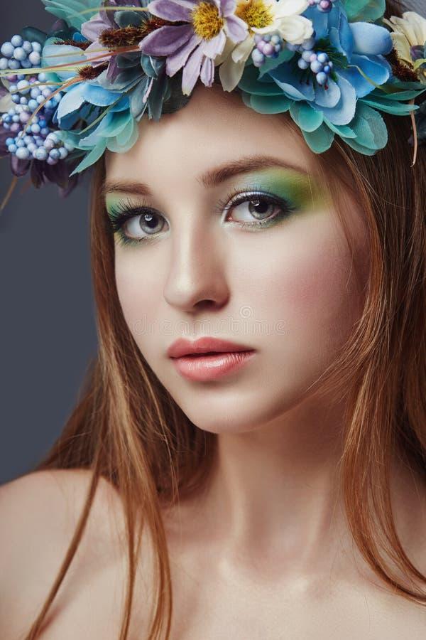 Frau mit einem Kranz von blauen Blumen auf ihrem Kopf Schönes Make-up und Blumen, natürliche saubere Haut, Sorgfalt und Hydratati lizenzfreie stockbilder