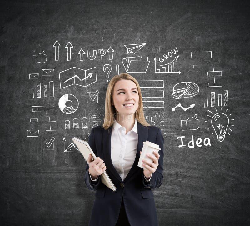 Frau mit einem Notizbuch und einer Kaffeetasse nahe einem Startidee sketc lizenzfreies stockfoto