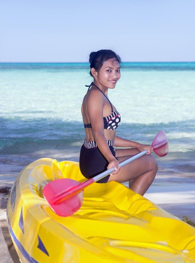Frau mit einem Paddel sitzt auf einem aufblasbaren Boot lizenzfreie stockfotografie