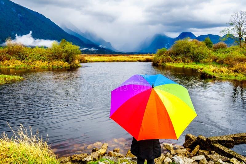 Frau mit einem Regenbogen farbigen Regenschirm unter dunklen Regenwolken an einem kalten Frühlingstag an den Lagunen von Pitt-Add stockfoto