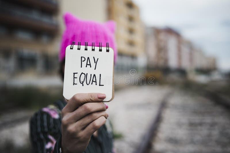 Frau mit einem rosa Hut und der Text zahlen Gleichgestelltes stockfotos