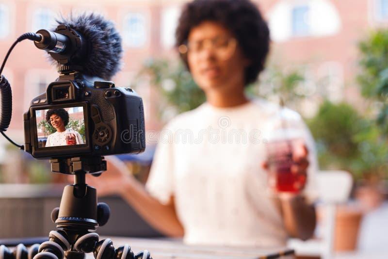 Frau mit einem Saft in einer Hand sprechend mit Digitalkamera lizenzfreie stockfotos