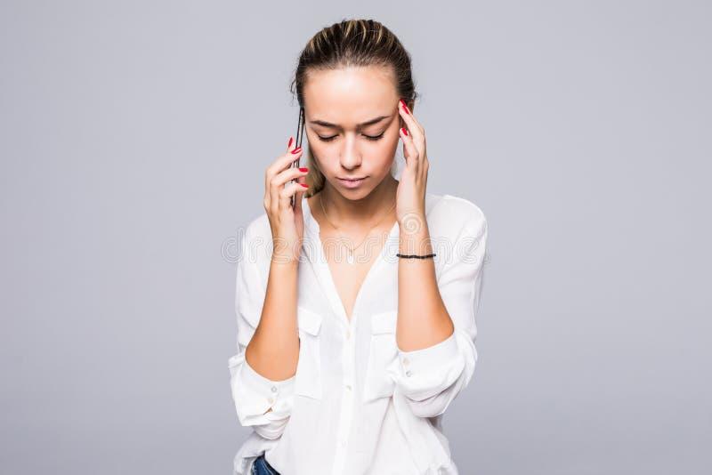 Frau mit einem schönen Gesichtsumkippen sprechend am Telefon auf lokalisiertem grauem Hintergrund lizenzfreie stockbilder