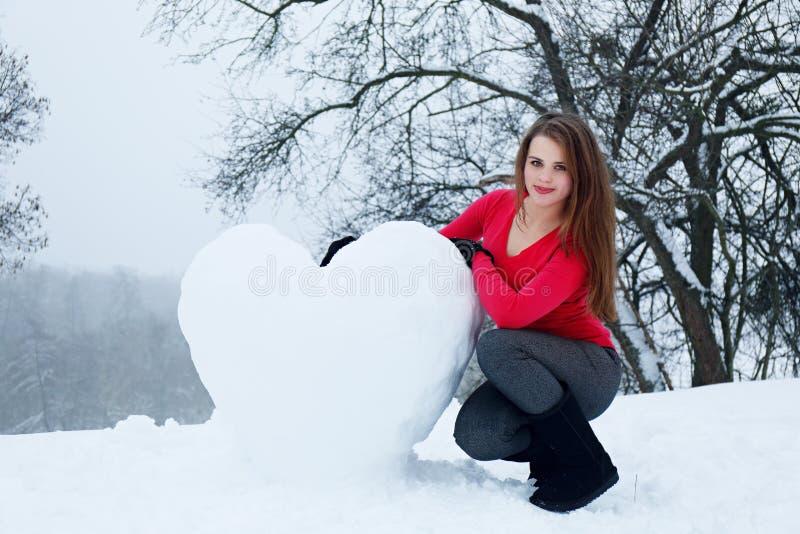 Frau mit einem schneebedeckten Herzen stockfoto