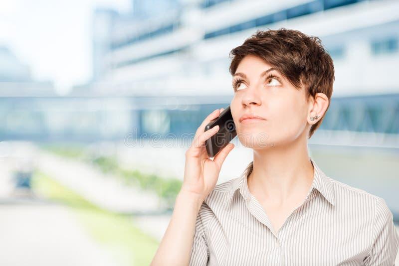 Frau mit einem Telefon, das Leerraum betrachtet stockfotografie